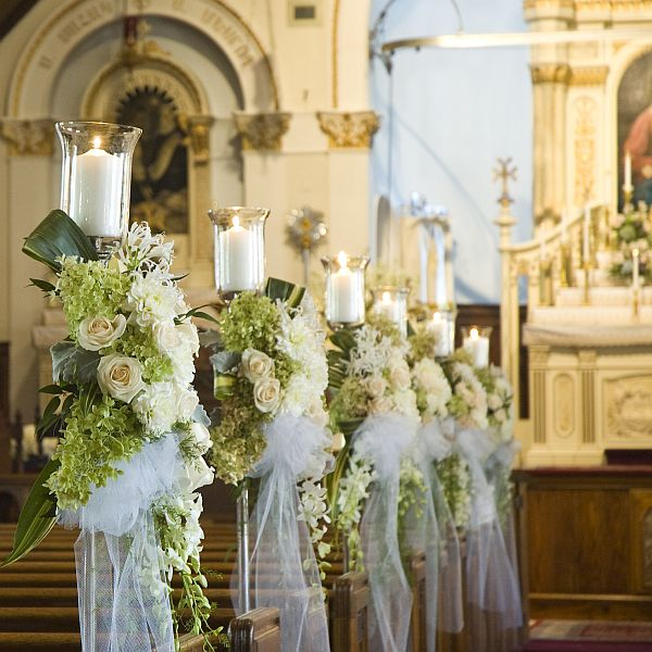 Row of cream wedding flowers with candles and white silk